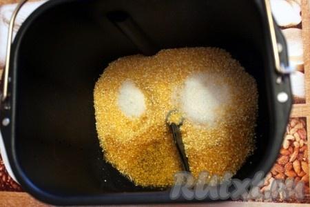 Первым делом вылить растительное масло на вращающуюся мешалку. Затем в контейнер хлебопечки высыпать кукурузную крупу, соль и сахар.