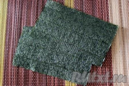 Стандартный лист нори разрезать пополам и положить 1 половинку блестящей стороной на циновку.